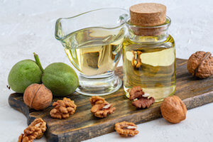 Walnut oil in a bottle and a glass cup.
