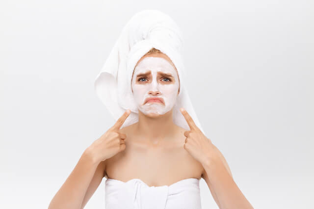 Unhappy beautiful young woman with white clay face mask makes acne therapy, wears white towel on hair, posing against white studio wall. Horizontal shot of Caucasian female with organic facial mask